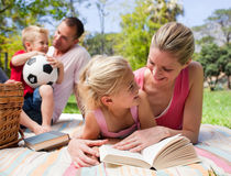 Mother and her daughter reading at a picnic Stock Photo
