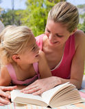 Mother and her daughter reading at a picnic Stock Photos