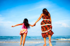 Mother and her daughter running together Stock Photo