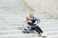 Mother and her daughter sit on steps. Stock Images
