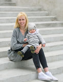 Mother and her daughter sit on steps. Royalty Free Stock Photography