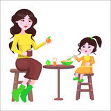 Mother and her Daughter Sit at the Table and Eat Royalty Free Stock Photography
