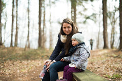 Mother with her daughter sitting on bench in forest Stock Photos