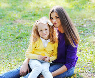 Mother with her daughter sitting on the grass Stock Photos