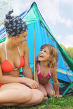 Mother and her daughter sitting near tent Stock Image