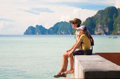 Mother with her daughter sitting next to the beach. Tropical view. Thailand Phi-Phi. royalty free stock photo