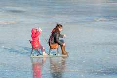 Mother and her daughter sitting on the sleigh Royalty Free Stock Image