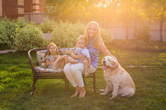 Mother and her daughter and son in the garden with a golden retriever dog Stock Images