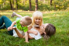Mother and her daughter and son together playing and laughing on the grass. Family concept, mother and her daughter and son together playing and laughing on the Royalty Free Stock Photography