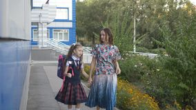Mother and her daughter, a student of the elementary school go home from school after lessons. stock footage