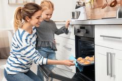 Mother and her daughter taking out cookies from oven. In kitchen royalty free stock image