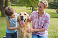 Mother and her daughter with their dog in the park Stock Photos