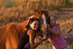 Mother and her daughter with their handsome horse Royalty Free Stock Photo