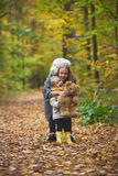 The mother, her daughter and toy Teddy bear posing and walking in autumn park Royalty Free Stock Images