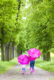Mother and her daughter with umbrellas Stock Images