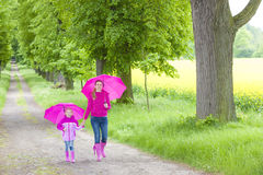Mother and her daughter with umbrellas. In spring alley Stock Photography
