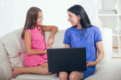 Mother and her daughter using a notebook Stock Photos
