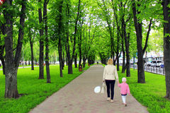 Mother and her daughter walk in city park Royalty Free Stock Image