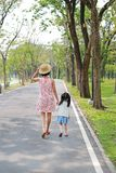 Mother and her daughter walking on the road and holding hands in the outdoor nature garden. Back view royalty free stock photo