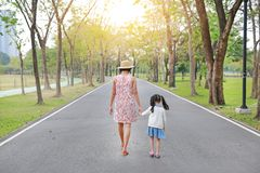 Mother and her daughter walking on the road and holding hands in the outdoor nature garden. Back view royalty free stock image