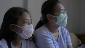Mother and her daughter are wearing protective mask to protect themselves from corona virus and staying together at home.