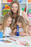 Mother with her daughters doing homework Stock Photo