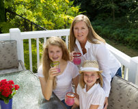 Mother and her daughters drinking grapefruit juice while outdoor Stock Photo
