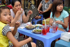 Mother with her daughters eating street food, sea snails with ve Stock Photos