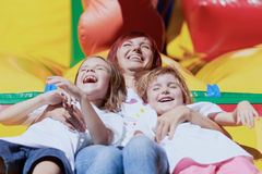 Mother and her daughters having fun on jumping castle. Mom and her daughters laughing out loud laying on a bouncing castle in a bright summer day outdoors Stock Photos