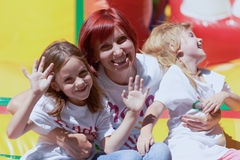 Mother and her daughters having fun on jumping castle. Young mother with her cute daughters waving you laughing on the bouncing castle outdoors in a bright sunny Royalty Free Stock Photography