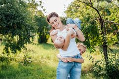 Mom and her daughters are walking in the summer park royalty free stock photo