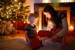 Mother and her daughters opening a Christmas gift Stock Photography