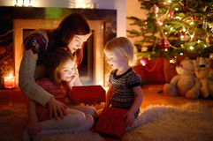 Mother and her daughters opening a Christmas gift Royalty Free Stock Image