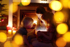 Mother and her daughters opening a Christmas gift royalty free stock photo
