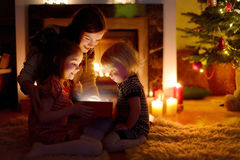 Mother and her daughters opening a Christmas gift Stock Photos