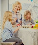 Mother and her daughters painting and decorating easter eggs. Cheerful mother and her daughters painting and decorating easter eggs Stock Image