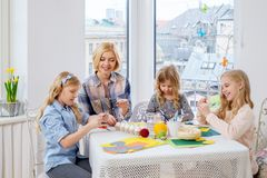 Mother and her daughters painting and decorating easter eggs. Royalty Free Stock Images