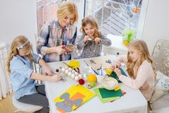 Mother and her daughters painting and decorating easter eggs. Cheerful mother and her daughters painting and decorating easter eggs Royalty Free Stock Images