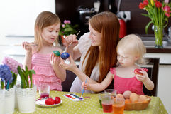 Mother and her daughters painting Easter eggs Stock Photography