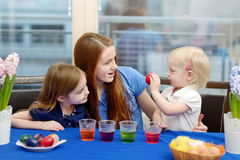 Mother and her daughters painting Easter eggs Stock Photo