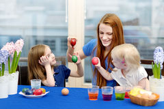 Mother and her daughters painting Easter eggs Stock Photos
