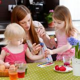 Mother and her daughters painting Easter eggs Stock Image