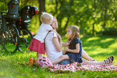 Mother and her daughters picnicking in the park Royalty Free Stock Image