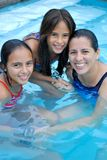 Mother with her daughters in  the pool. A young, happy, beautiful girls in a pool with their mom Stock Photos