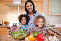 Mother and her daughters preparing salad Stock Images