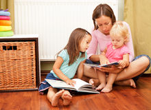 Mother with her daughters reading a book Stock Image
