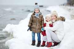 Mother and her daughters by the sea on winter Stock Photos