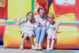 Mother and her daughters sitting on bouncing castle Stock Photos