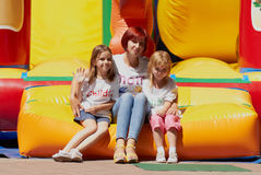Mother and her daughters sitting on jumping castle. Young loving mother with her cute daughters sitting on the bouncing castle outdoors in a bright sunny day Stock Photos