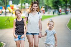 Mother with her daughters walking in the park stock image
